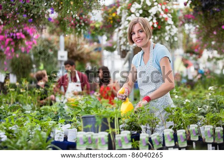 Portrait of young woman spraying plants - stock photo