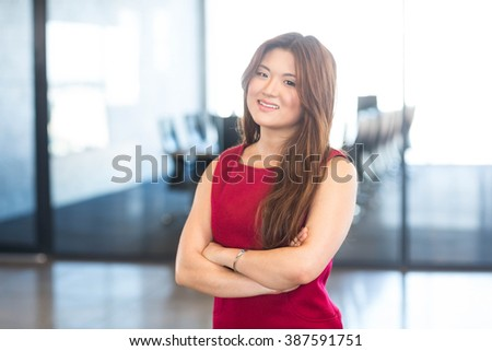 Portrait of young woman standing in front of conference room in office - stock photo