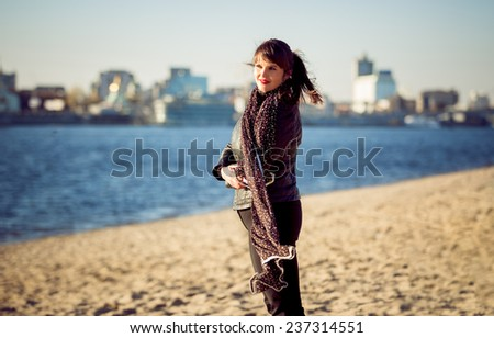 Portrait of young woman standing on beach at windy autumn day - stock photo