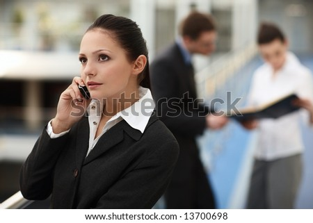 Portrait of young woman standing talking on the phone in modern business office building corridor - stock photo