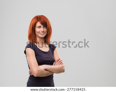 portrait of young woman standing with crossed arms and smiling, against grey background - stock photo