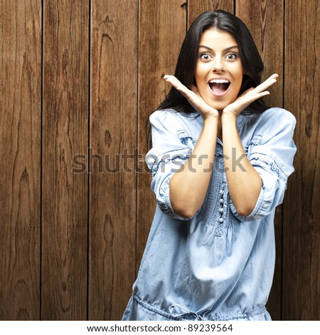portrait of young woman surprised against a wooden wall