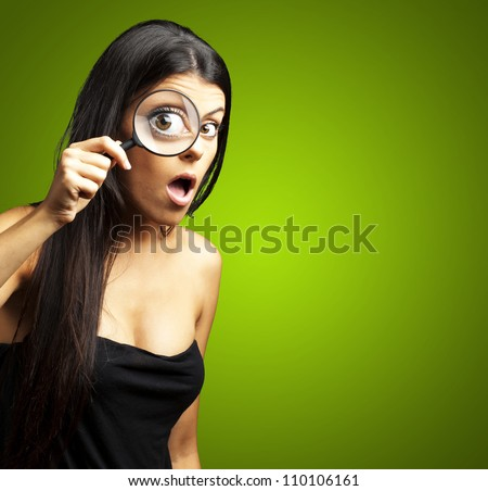 portrait of young woman surprised looking through a magnifying glass over green - stock photo