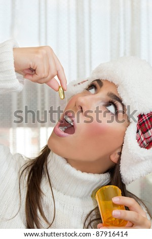 Portrait of young woman taking an  Omega 3 fish oil capsule. - stock photo