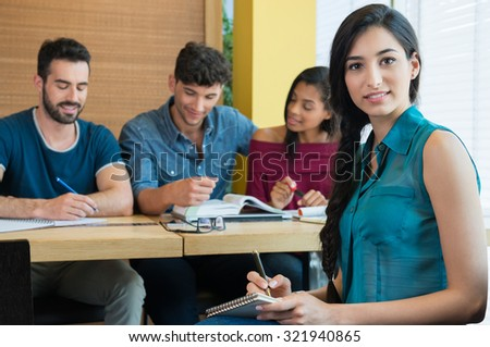 Portrait of young woman taking down note in notebook. Female student looking at camera and smiling. Happy student writing with other students studying in background. - stock photo