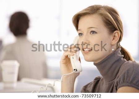 Portrait of young woman talking on landline phone. Looking at camera, smiling.
