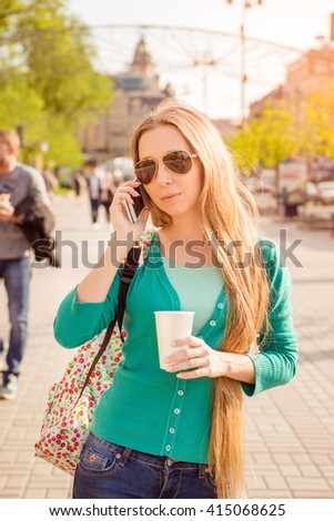 Portrait of young woman talking on phone and drinking coffee - stock photo
