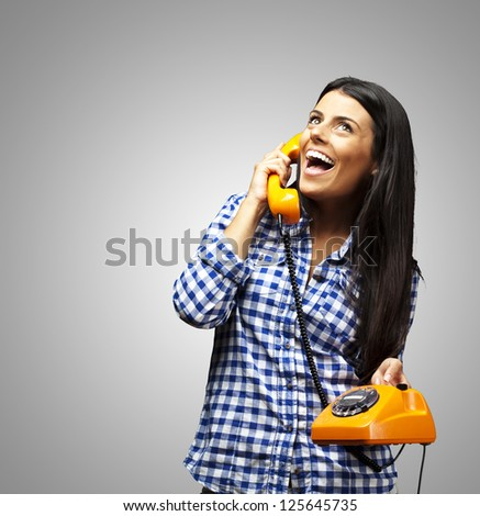 portrait of young woman talking on vintage telephone over grey - stock photo