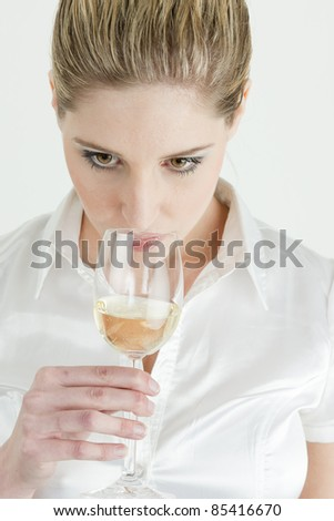 portrait of young woman tasting white wine - stock photo
