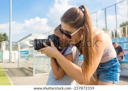 Portrait of young woman teaching little girl to photograph using professional camera - stock photo
