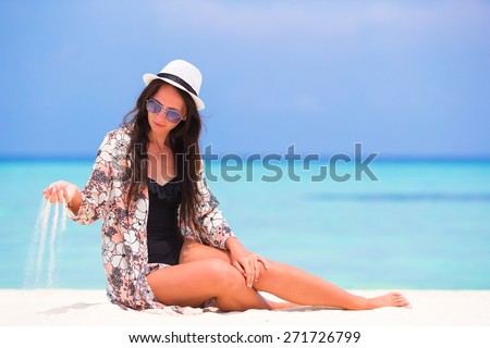 Portrait of young woman throwing sand on beach during summer vacation