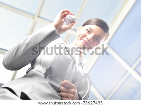 Portrait of young woman throwing wad into basket in sun beam. Ecological trash wasting concept. - stock photo