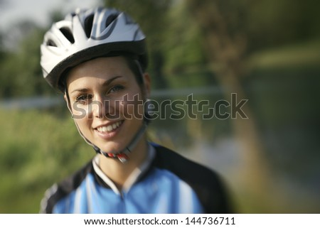 portrait of young woman training on mountain bike and smiling at camera. Defocused image - stock photo