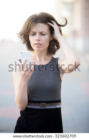 Portrait of young woman using cellphone on the street in summer, looking at screen in dismay, holding her head with lost and worried facial expression - stock photo