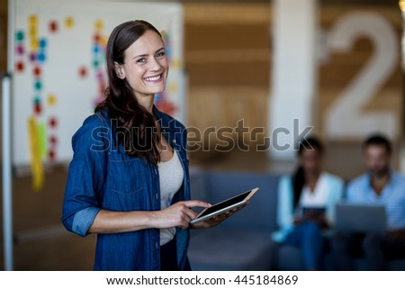 Portrait of young woman using digital tablet in the office