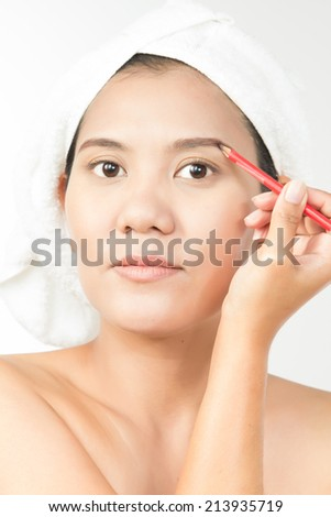 Portrait of young woman using eyebrows pencil - stock photo