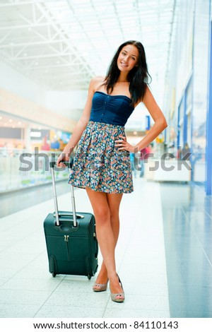 Portrait of young woman walking inside modern international airport with suitcase to boarding gates