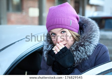 Portrait of young woman warming her hands near the car - stock photo