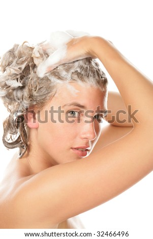 Portrait of young woman washing her hair isolated on white background - stock photo