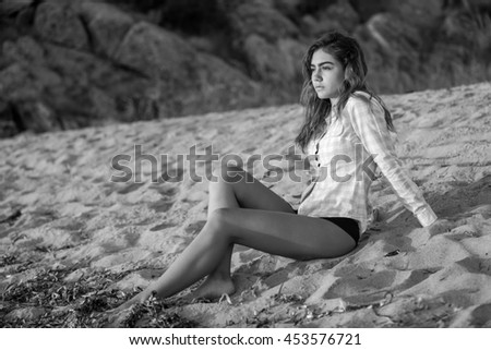 Portrait of young woman watching the sunrise at the beach.