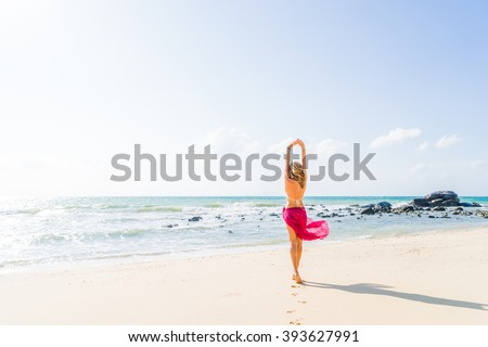 Portrait of young woman wearing a pink sarong and bikini on the tropical beach - stock photo