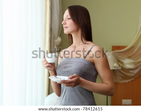 portrait of young woman wearing dress robe holding a cup of tea - stock photo