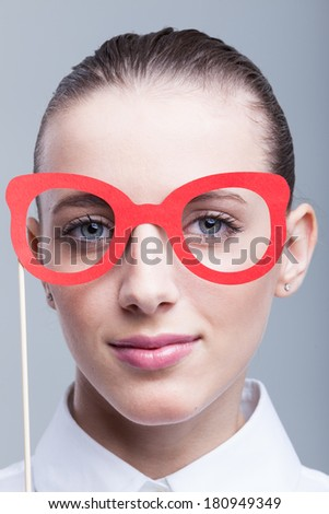 Portrait of young woman wearing funny eyeglass mask - stock photo