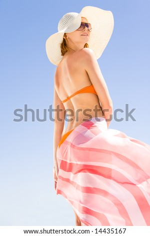 Portrait of young woman wearing hat, sunglasses, bikini and pareo standing on    background of clear sky - stock photo