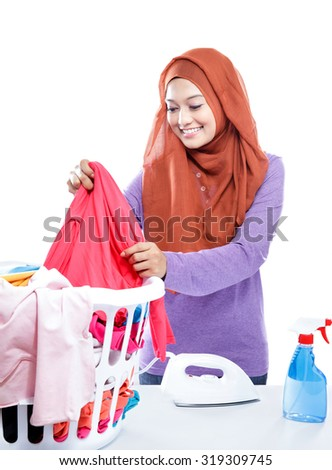 portrait of young woman wearing hijab ironing while pick up a clothes isolated on white - stock photo