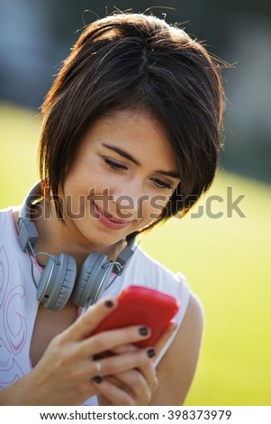 Portrait of young woman wearing sports clothing using mobile telephone.  In the background green field