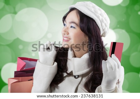 Portrait of young woman wearing winter coat, smiling happy while carrying shopping bags and holding credit card - stock photo