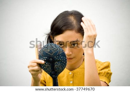 Portrait of Young Woman with a Bald Problems Grooming using Hand Mirror and Hairbrush Isolated on White