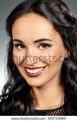 Portrait of young woman with a beautiful smile and healthy teeth. Teeth braces. Studio shot. - stock photo