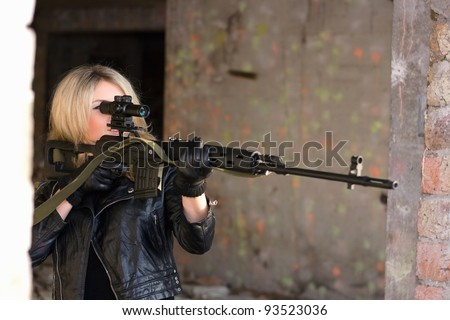 Portrait of young woman with a sniper rifle - stock photo
