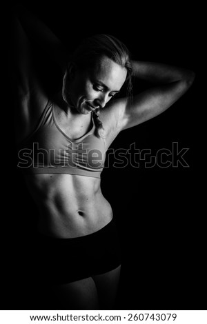 Portrait of young woman with abdominal muscles in black and white