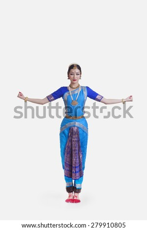 Portrait of young woman with arms outstretched performing Bharatanatyam against white background