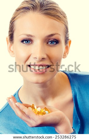 Portrait of young woman with assorted pills and capsules - stock photo