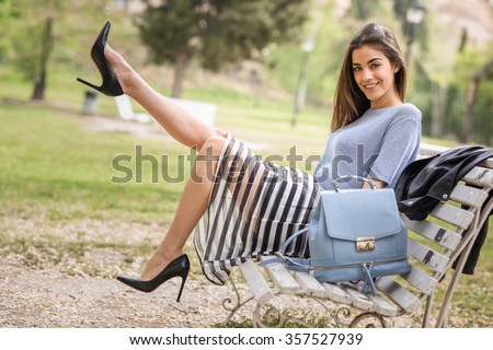 Portrait of young woman with beautiful legs in urban park wearing casual clothes. Girl wearing striped skirt, sweater and high heels