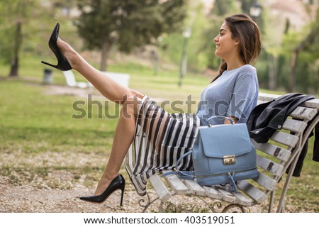 Portrait of young woman with beautiful legs in urban park wearing casual clothes. Girl wearing striped skirt, sweater and high heels - stock photo