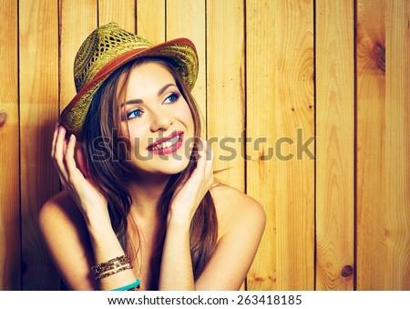 Portrait of young woman with big toothy smile. Country style model posing against wooden background. - stock photo