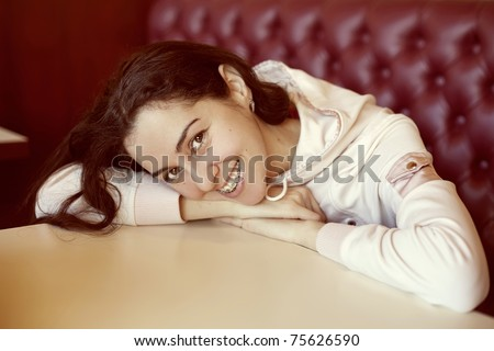 Portrait of young woman with brackets in cafe - stock photo