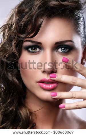 Portrait of young woman with bright make-up and manicure - stock photo