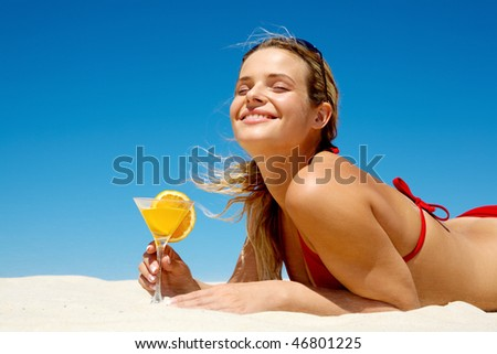 Portrait of young woman with closed eyes holding orange juice - stock photo