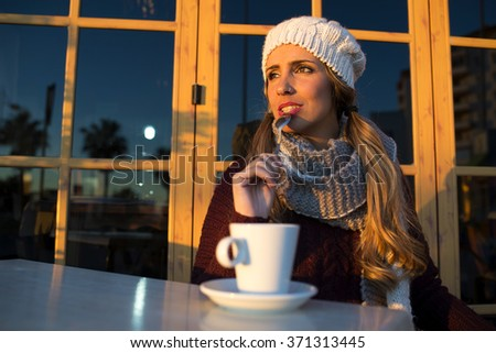 Portrait of young woman with coffee and spoon in mouth. - stock photo