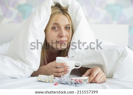 Portrait of young woman with coffee mug and medicines suffering from fever while covered in quilt on bed - stock photo