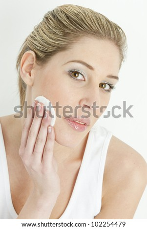 portrait of young woman with cotton pad - stock photo