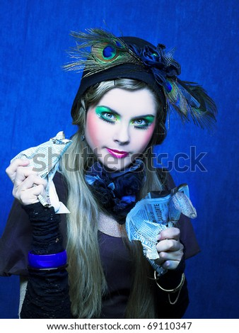 Portrait of young woman with creative make-up and in vintage hat. - stock photo