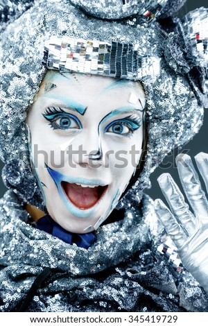 Portrait of young woman with creative silver make-up for carnival - stock photo
