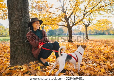 Portrait of young woman with cute dog sitting under tree in autumn park - stock photo