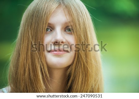 Portrait of young woman with face covered with hair at summer green park.